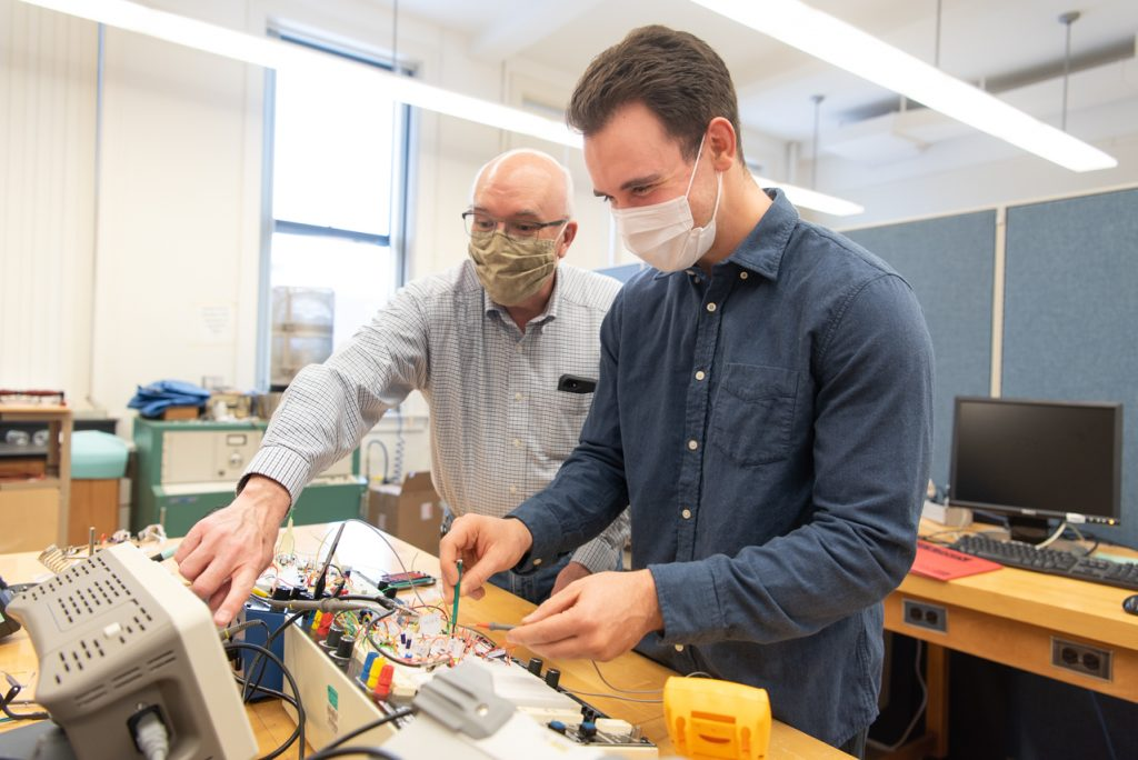 Dr. George Rutherford (left) and Zach Mobille '19 working with their electronic circuit.
