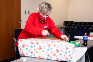 Holiday help wraps a gift.