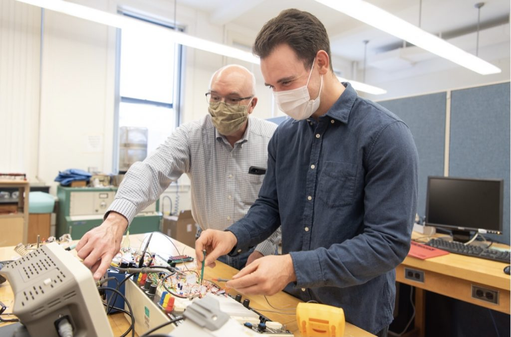 Associate Professor of Physics Dr. George Rutherford and Zach Mobille work with their electronic circuit.