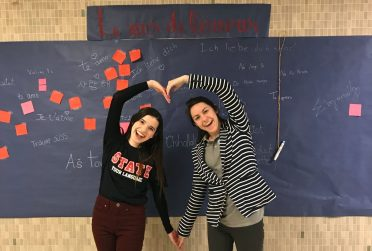 Two people making a heart out of their arms