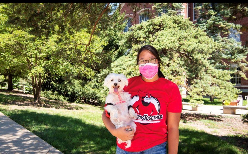 student standing outside holding white dog
