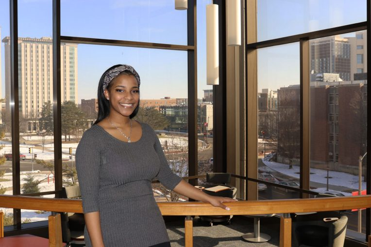 photo of student scholarship recipient Tenaya Muhammad in front of the Floor 4 SE windows with a view of Hewitt and Watterson Towers in background