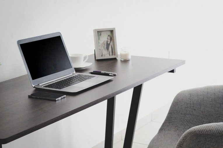 lap top on a wood desk next to a chair