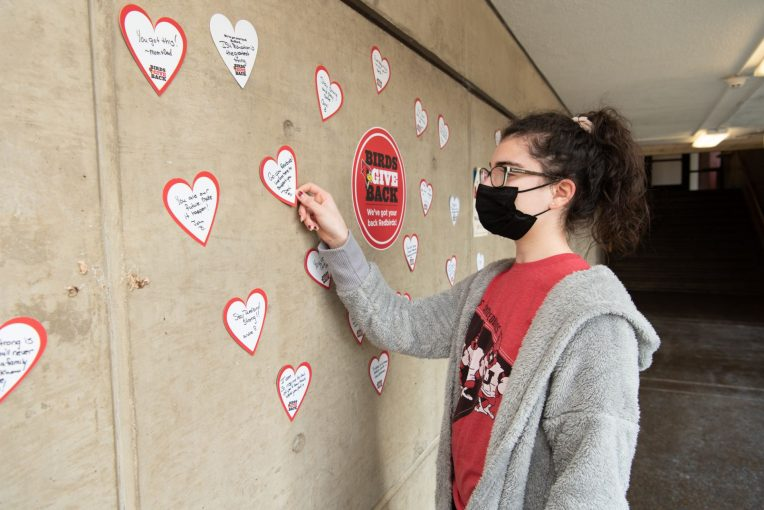 Student reading a heart shaped message on a wall