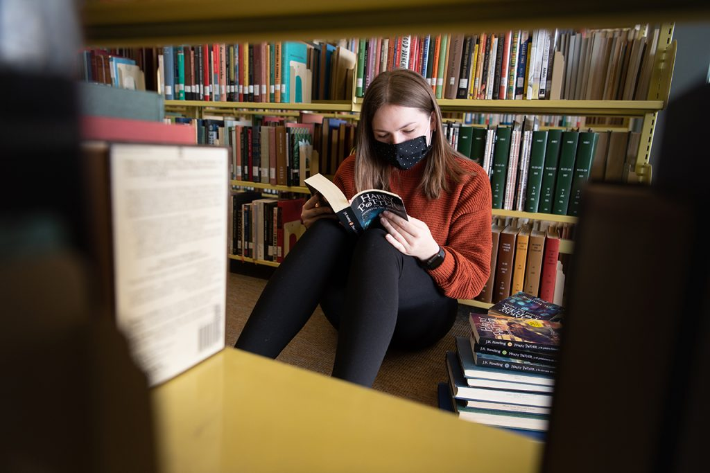 Woman sits on the ground reading in with a stack of books next to her
