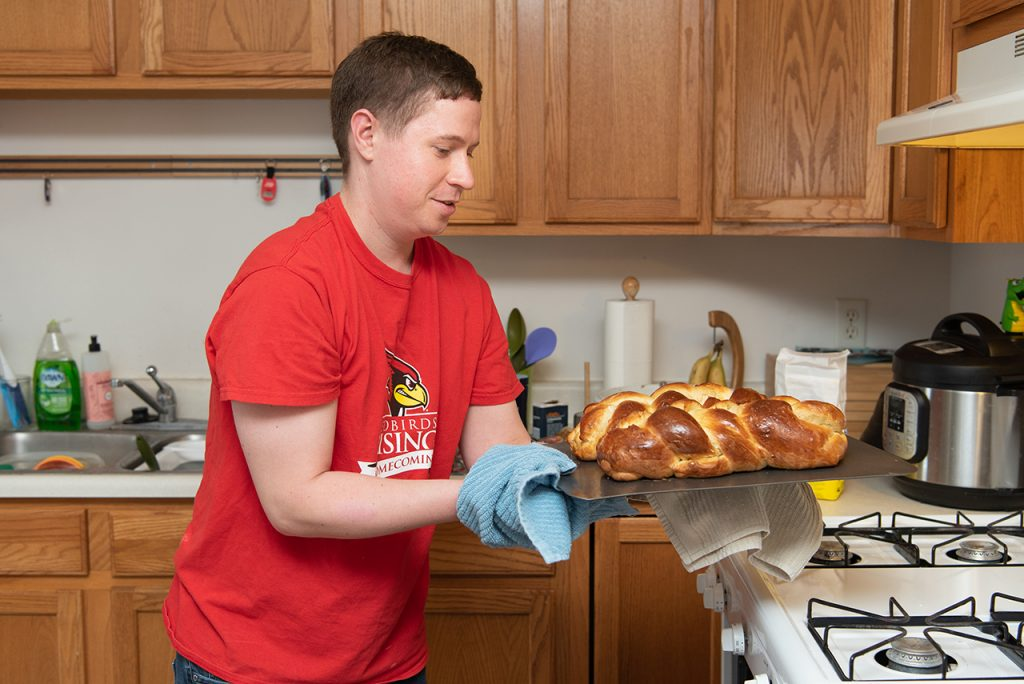 Man removes bread from an oven