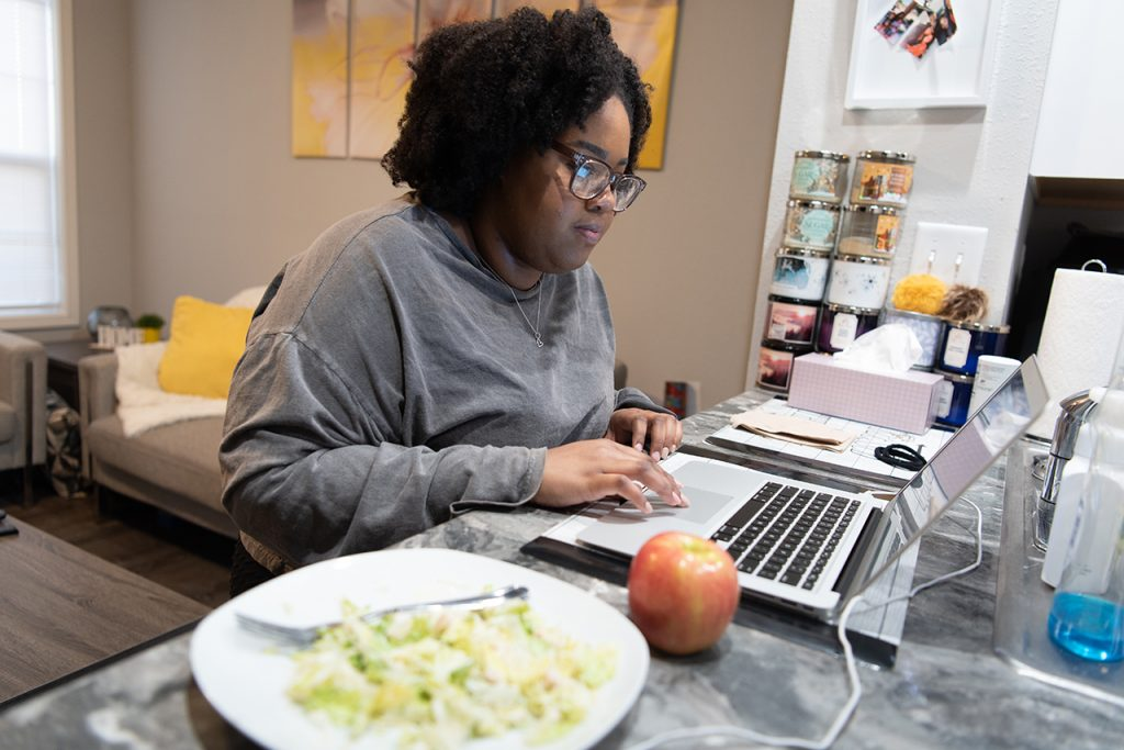 Lauren Harris reads over notes for the upcoming Student Government Association meetings while having an apple and salad for dinner.