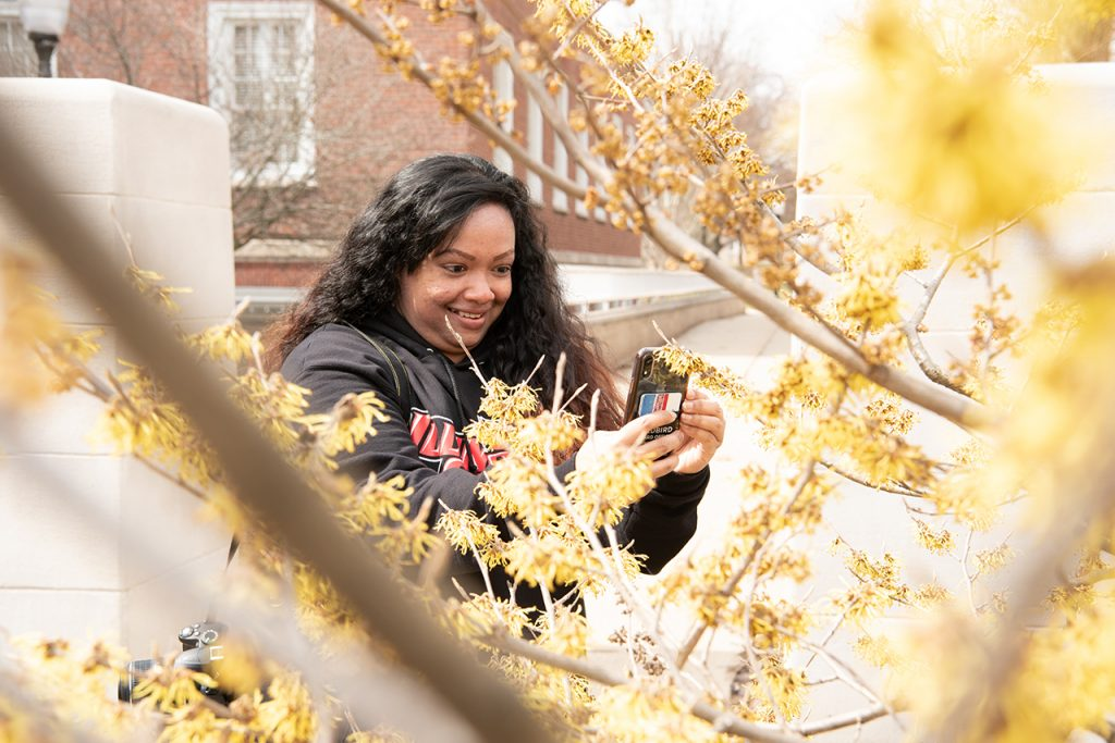 Woman takes photo of bush on campus