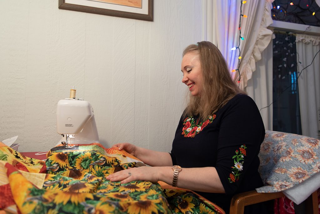 Woman looks down on quilt she is stitching