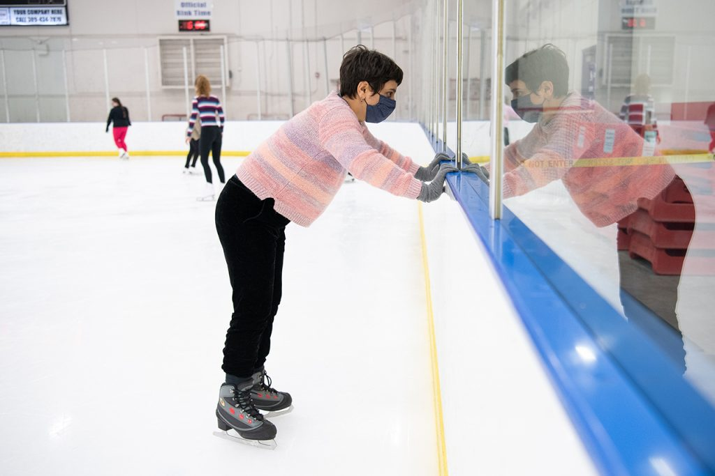 Woman on skates looking through plexiglass at hockey rink.