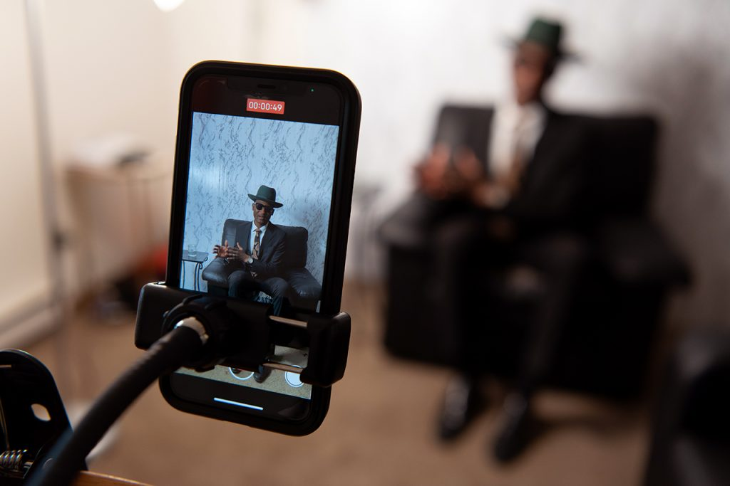 Phone, in focus, recording a man talking in a leather chair