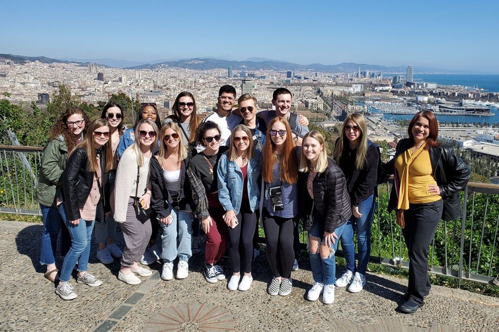 Dr. Rivadeneyra and fifteen students pose by the sea during their Spring 2021 study abroad in Spain.