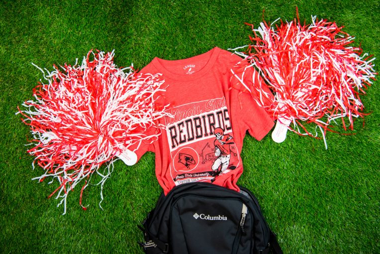 Red Redbird t-shirt with a football player on it coming out of a backpack with pom poms by each sleeve as if it were cheering