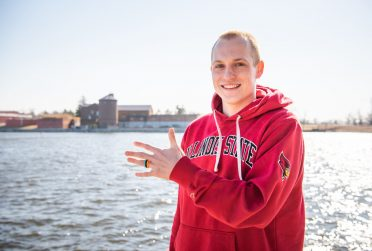 Cody Rogers standing in front of Lake Bloomington, wearing one of the rings that his company produces