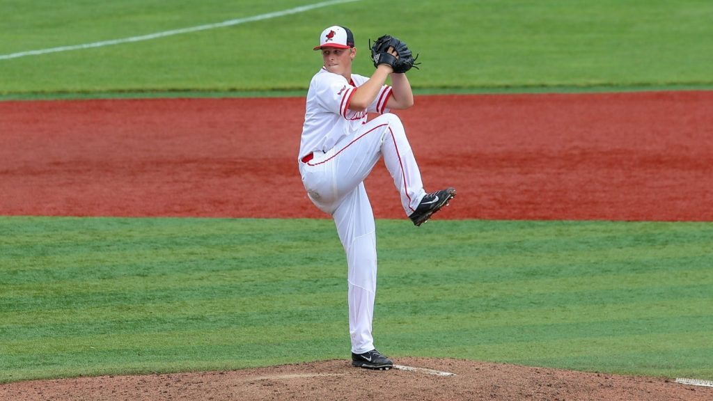 Left-handed pitcher winds up to pitch on the mound.