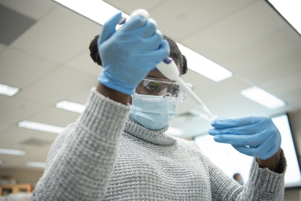 Audrey Eshun uses a micropipette to transfer a small amount of DNA containing solution into an Eppendorf tube.