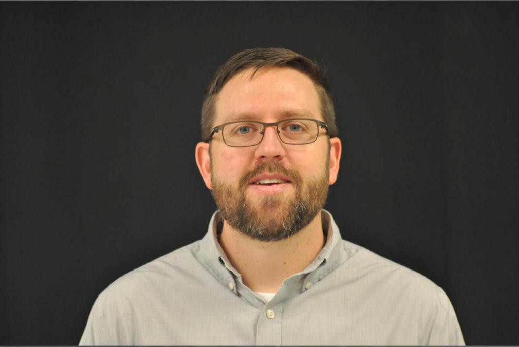 faculty member headshot on black backdrop
