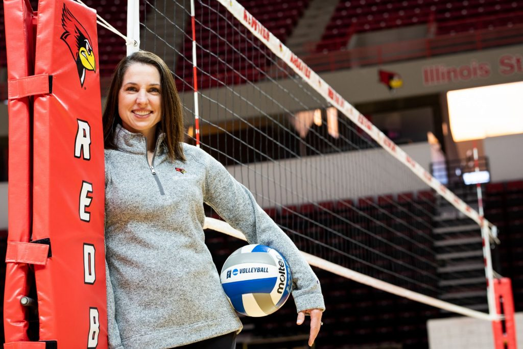 Leah Johnson posing with volleyball in front of net
