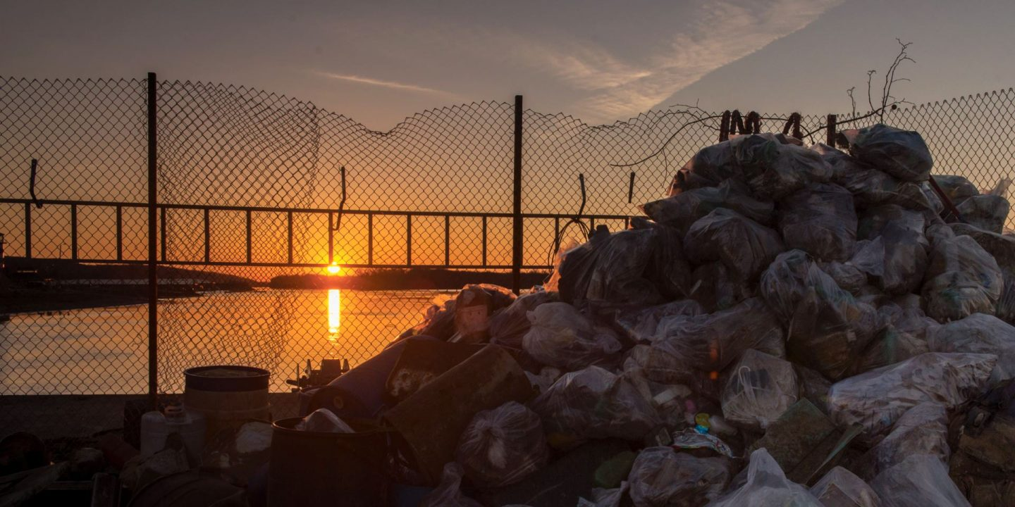 Redbird Impact cover Fall 2018 no text image of Mississippi River with a bridge in the background and a pile of trash in the foreground