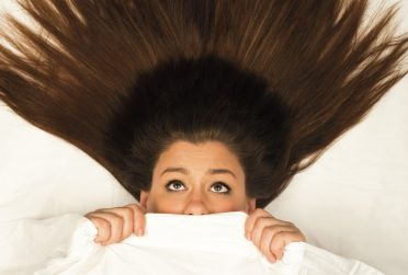 Redbird Scholar Fall 2016 cover textless with woman under bed sheets looking scared with hair stretching above her head