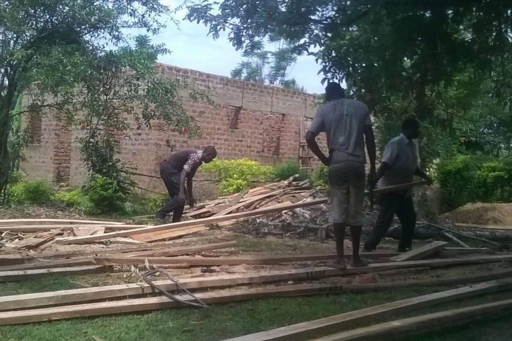 three people handling pieces of wood working to build a library in Uganda. Photo courtesy of Libraries for the World
