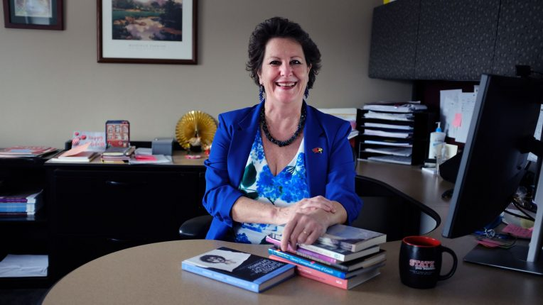 Distinguished Professor Dr. Roberta Seelinger Trites seated at her desk with her books