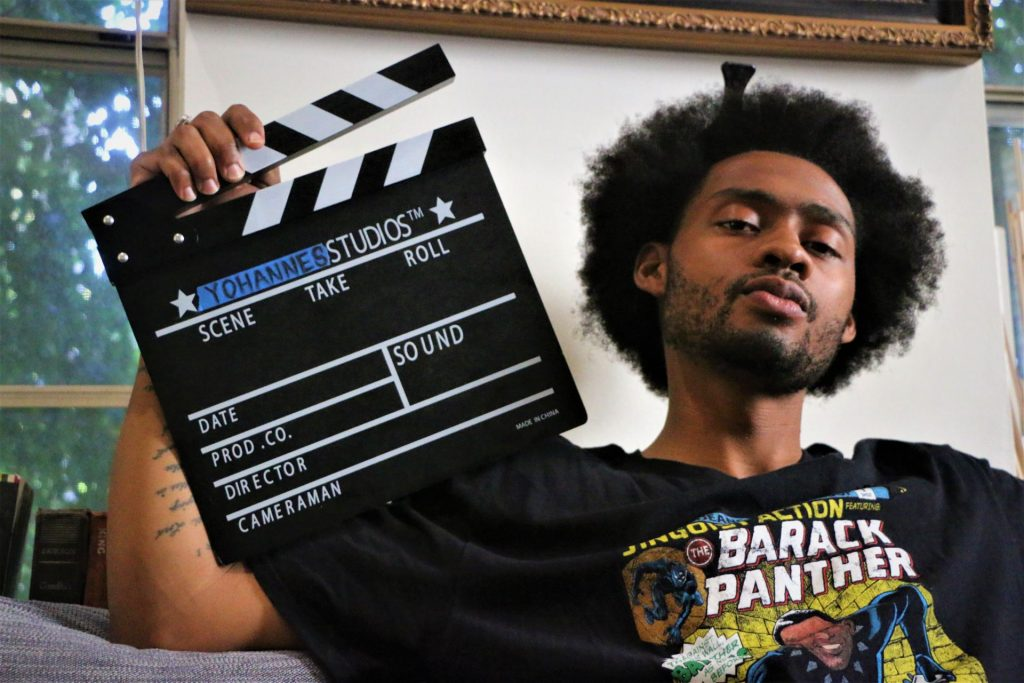 Yohannes Yamassee '16 posing with his clapperboard.