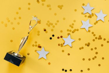 A gold trophy, confetti, and gold stars