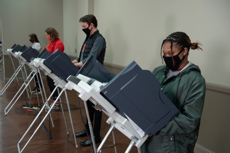 masked voters at distanced voting machines