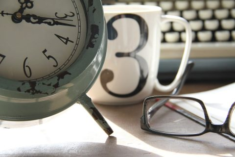 Clock next to a coffee mug with No. 3, glasses, and a keyboard
