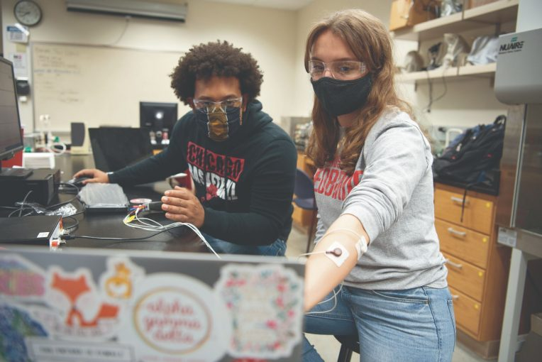 Two students work in a lab together.