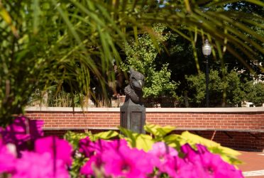 The bust of Reggie Redbird framed by purple flowers and green leaves