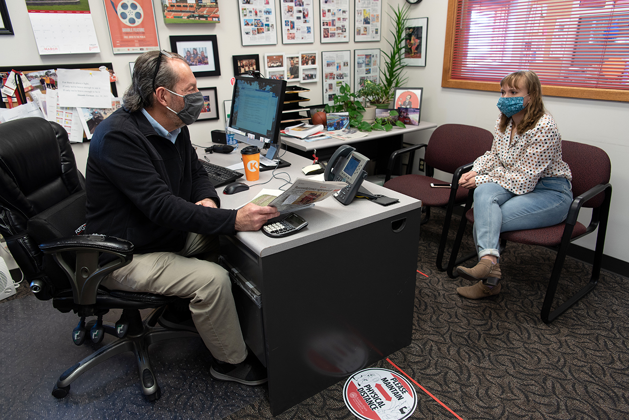 Student talks with a faculty member in an office