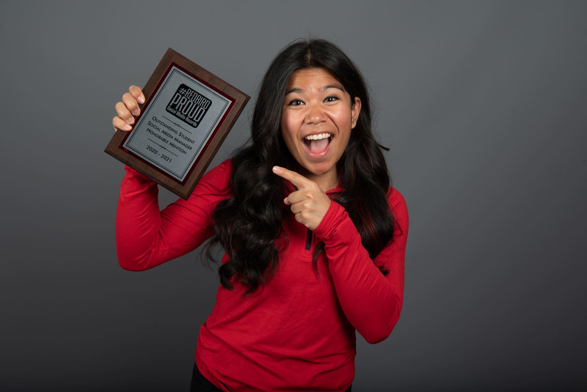 Leia Atas posed with award