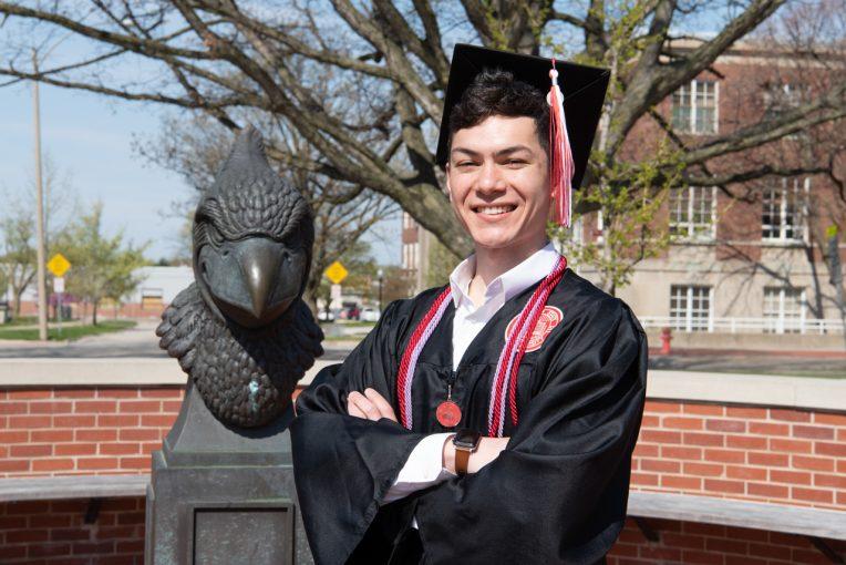 Isaac Faamoe on campus in his graduation regalia
