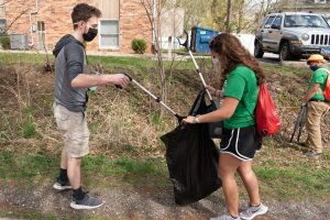 students picking up trash and putting it in a garbage bag