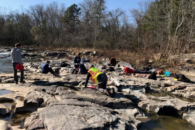 Assistant Professor of Geology Dr. Tenley Banik's students observing complex rocks near the Tiemann Shut-Ins, Missouri.