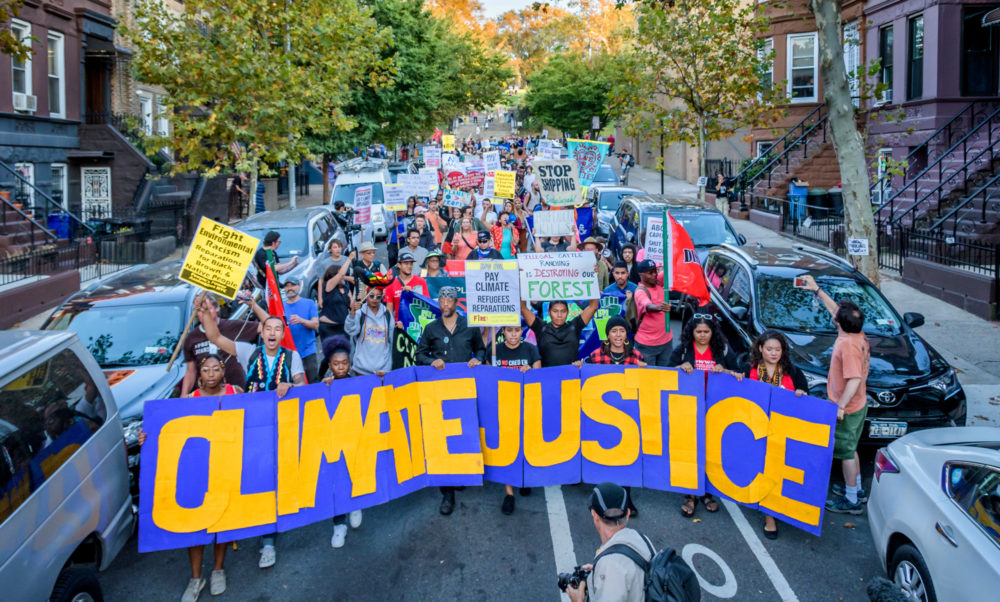 March and people holding banner reading Climate Justice