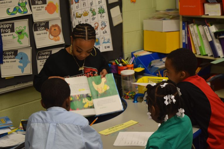 Student teacher reading to students