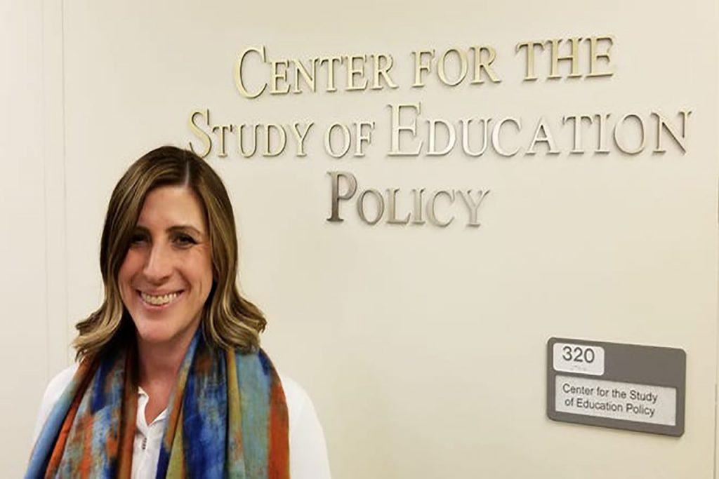 """Woman stands in front of a sign that reads """"Center For the Study of Education Policy"""""""