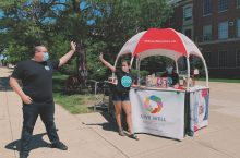 Two people pretending to clap hands at a Live Well booth on the Quad