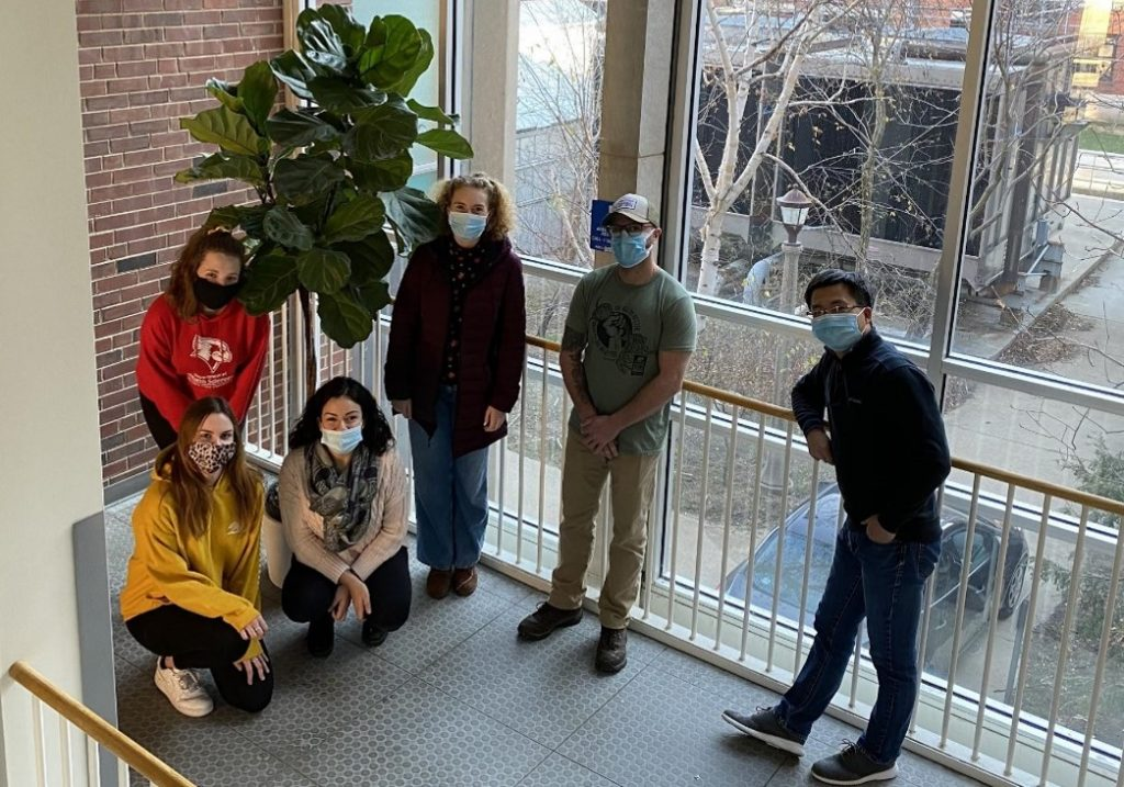 Students and faculty member in middle of stairwell by a plant.