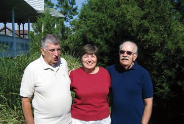 Siblings David, Charlotte, and Fred Roberts smile for a photo.