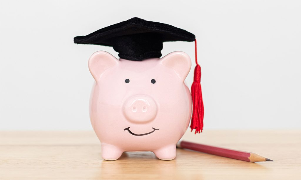 piggy bank with graduation hat and pencil