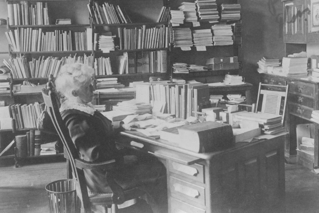 Black and white photograph of Angeline (Ange) V. Milner, first librarian at Illinois State Normal University. Milner is shown sitting at her office desk. Date unknown.