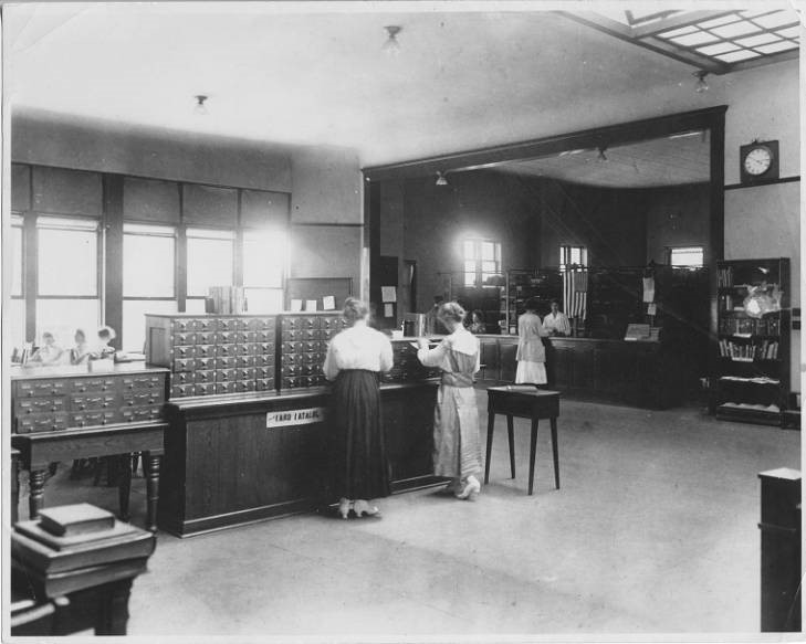 A black and white photograph of students using the card catalog when the library was located in North Hall