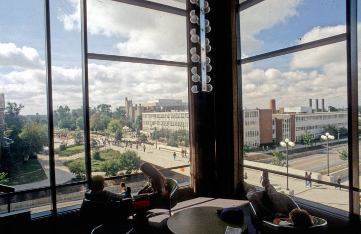 Students studying in corner of Floor 4 with the College Avenue Bridge and Schroeder Hall visible out the windows. Photograph from 1980.