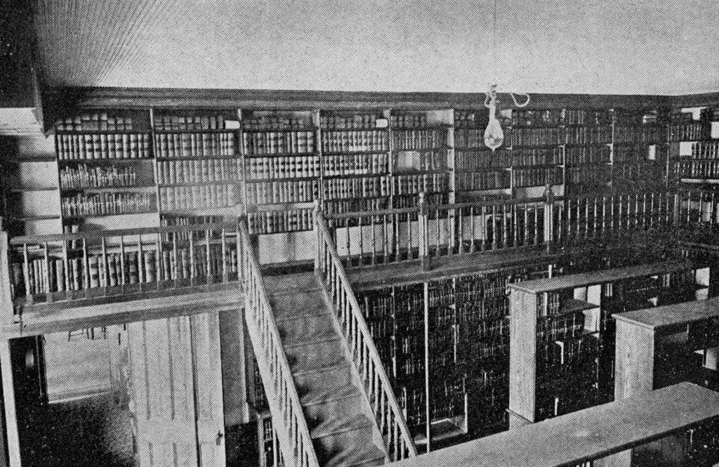 Black and white photograph of the University's library when it was Old Main consisting of a room with books on shelves and then a second floor balcony area with a wall of bookshelves.
