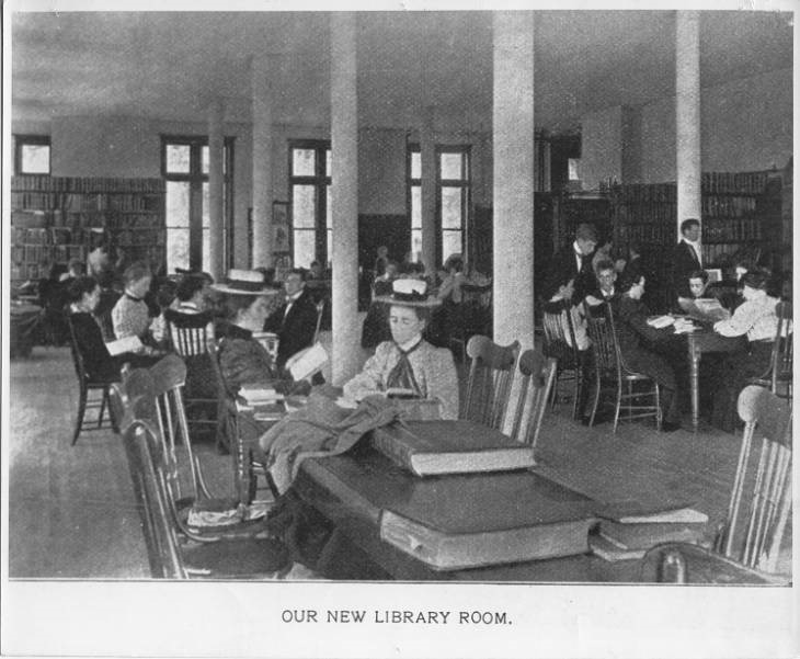 Black and white photograph of students in the library's reading room when it was located in Cook Hall. Students sitting at tables with windows and books in background.