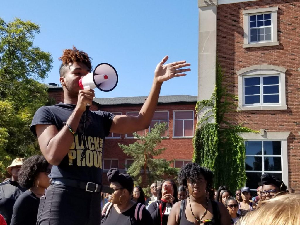 person holding megaphone in front of crowd